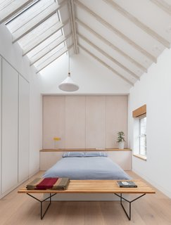 Whitewashed spruce rafters in the bedroom express the grain of the wood and serve as a canvas for light play.