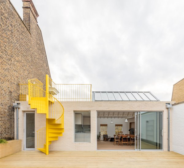 The brick-clad rooftop apartment on Mile End Road in East London features a vibrant yellow spiral staircase that links the upper and the lower terrace.