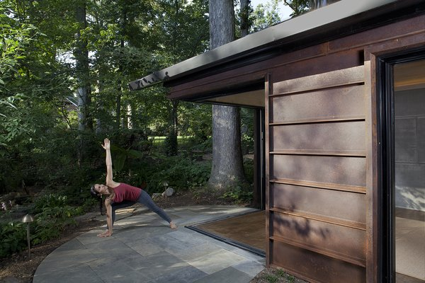 Glass pocket doors slide away, opening the cabin to its wooded surround. Bluestone pavers on the exterior contrast with the warm tone of the Cor-Ten steel siding.