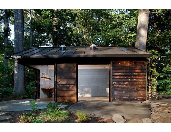 The materiality of the cabin blends into its wooded surround.