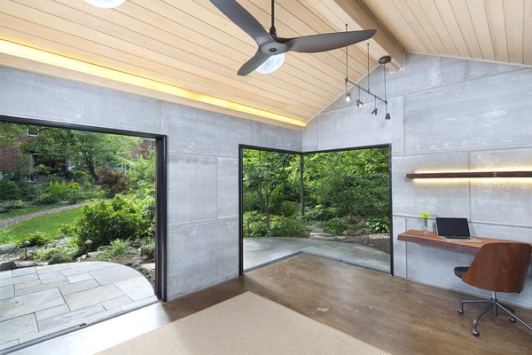 The interior of the cabin maintains a minimalist aesthetic so that the lush landscape is the main focus. The concrete floors are stained a medium brown tone, while the ceiling features tongue-and-groove clear pine with a pickled finish; the walls are sided with grouted cement board.