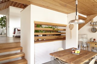 The property's descending grade allowed the architects to create a split-level home so that the dining area steps down from the living space.