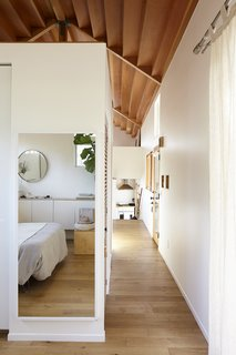 The rooms of the cottage are defined by partial walls; the vaulted ceiling hovers above the partial walls and unites the various spaces.