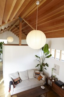 A globe-like pendant suspends from the stepped Douglas Fir ceiling in the living room.