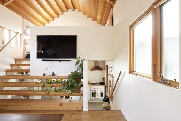 A timber staircase accesses the loft-like office and is wider at the bottom, where it doubles as shelving.