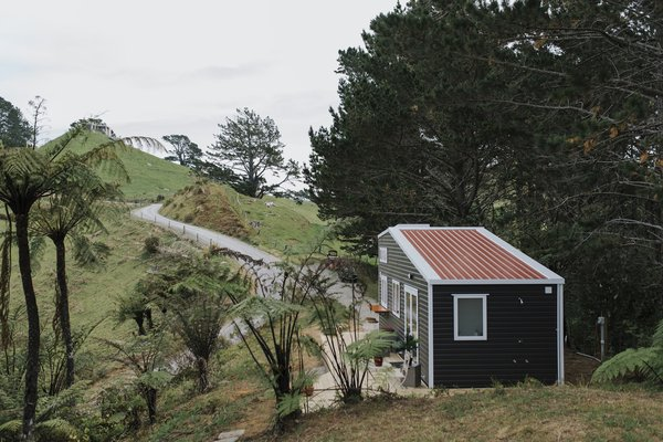 The bright red standing-seam metal roof (viewed from the main house) helped inspire the tiny home's name: Cherry Picker.
