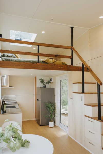 The loft bedroom is situated above the kitchen. The staircase is outfitted with drawers and a tall cabinet for cooking tools.