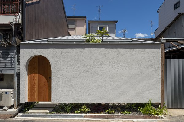 The stucco-clad tiny home is punctuated by archways, including the arched entrance, and two courtyards—one of which peeks out from beneath the cantilevered front facade.