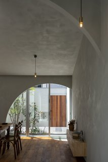 Lime plaster walls lend rich texture to the interior, absorbing and reflecting sunlight that pours in through an archway that frames the front courtyard.