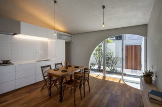 In the kitchen/dining area, the architects suspended brass pendants with a slim silhouette that let the adjacent courtyard be the room's focal point.