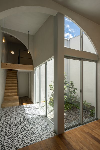 The arches frame views of the sky as well as the interior courtyard. Southeast Asian floor tile marks the transition from the kitchen/dining area to the courtyard and the second level.