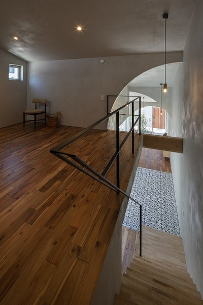 A simple metal railing and Red Acacia flooring create a minimalist aesthetic for the loft area.