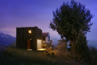 The compact residence, sided with tarred pine and glass, is surrounded by the Andes mountains.