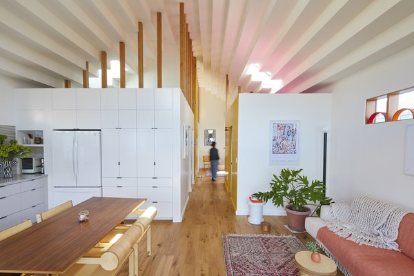 A stepped drywall ceiling lends texture and interest on the interior. The open-plan public space, which includes the kitchen, dining area, and living room, is sectioned by a pair of box-like volumes that contain the two bathrooms; the two bedrooms are located at the rear of the house.