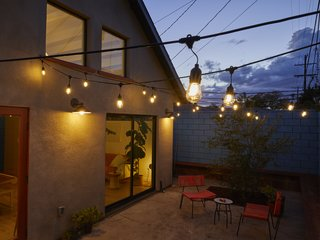 Outdoor string lights help to bathe the adjacent courtyard in a soft glow.