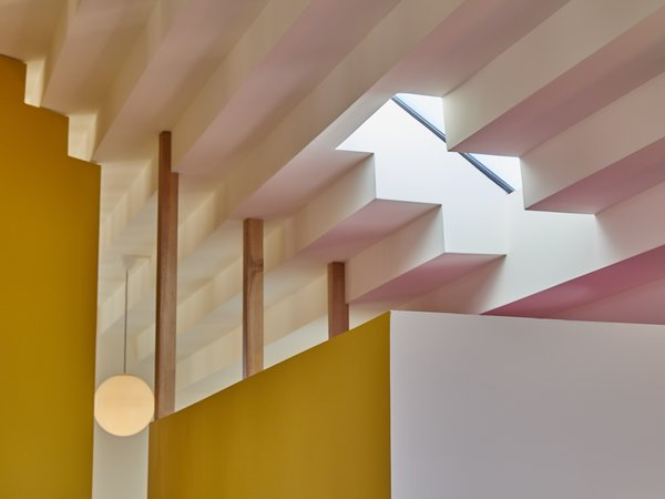 Sundius and Ichiki employed a white-painted, stepped ceiling that's made from drywall and reflects a bright, yellow wall and door and the pink tone that accents the bathroom skylight.