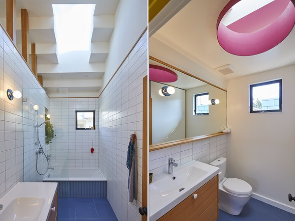 Left: The designers placed a sink vanity and a bathing area in one of the baths, where a rectangular skylight floods the space with sunshine. Right: The second bath, where there's a sink vanity and a toilet, features an oval-shaped skylight accented with a brilliant shade of hot pink.