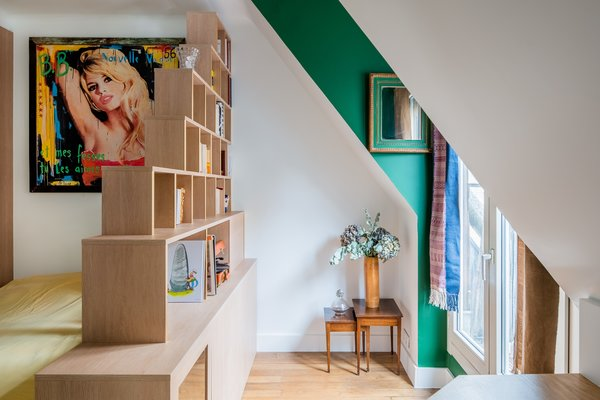 An artwork that depicts Brigitte Bardot and quotes from Jean Luc Godard's 1963 film Le Mepris hangs above the bed, lending vibrancy and whimsy.