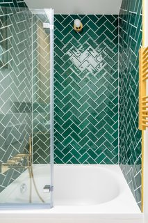 The addition of a skylight lets sunlight wash over jade-green tile that's laid in a herringbone pattern in the bathroom.
