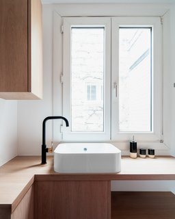 A black sink fixture accented with rose gold adds a contemporary note in the light-filled kitchen.