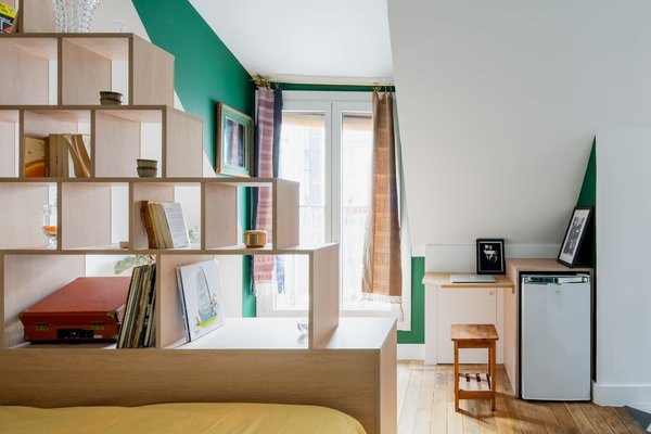 A small desk and a refrigerator are arranged beneath the sloped wall and ceiling in the sitting area adjacent to the bedroom.