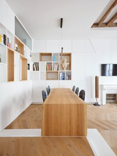 Petillaut designed a modernist built-in oak table that cantilevers in the dining room, preserving space in the open-plan area. Custom chairs with a slim silhouette also help to conserve space and create an airy quality for the room.