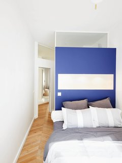"""""""Both of the bedrooms are master bedrooms,"""" Petillault says. """"The partition wall was an opportunity to do a beautifully colored, space-saving headboard and face the bed toward the window."""""""