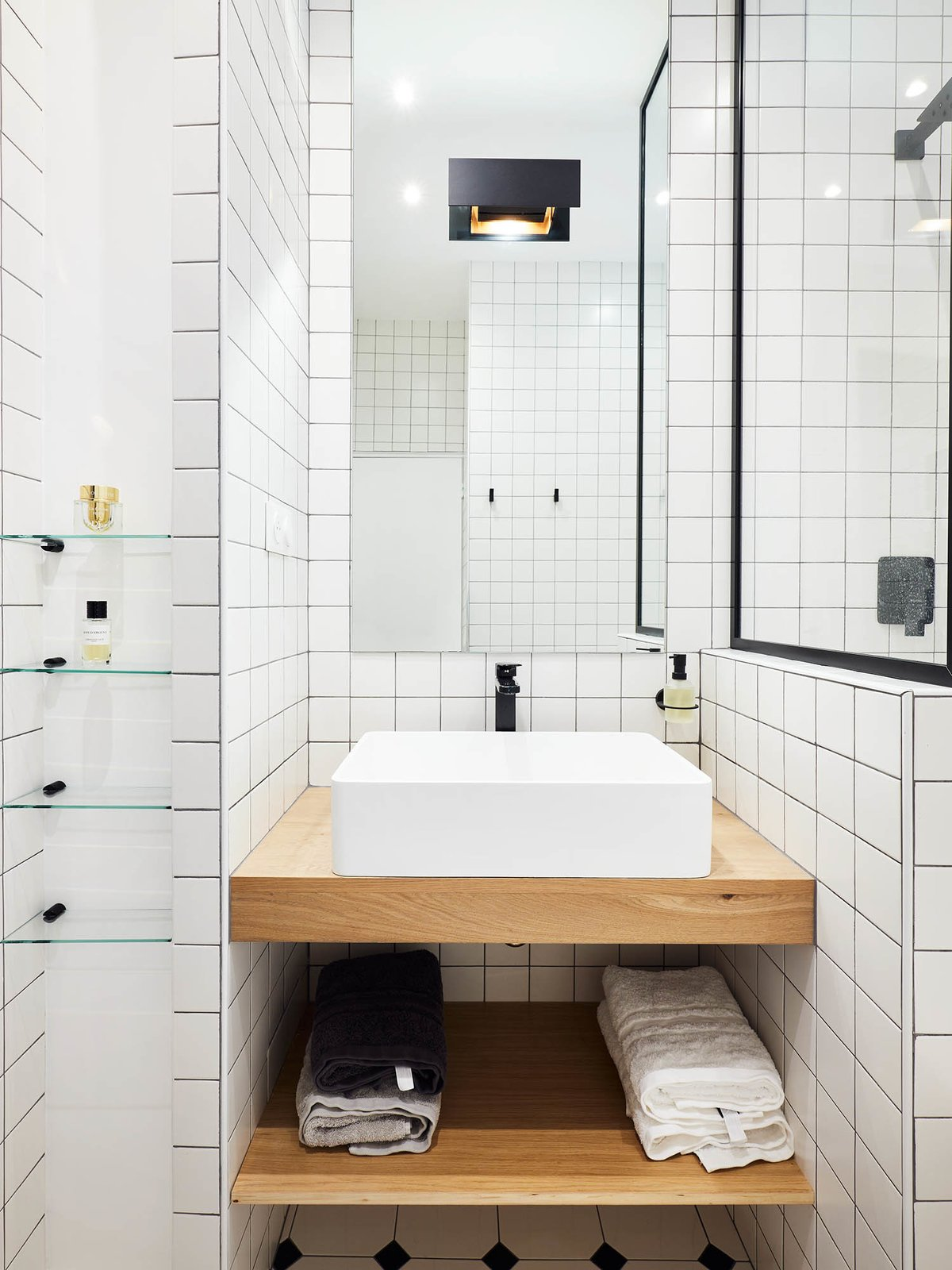 """Bath Room, Wood Counter, Vessel Sink, Corner Shower, Porcelain Tile Wall, Wall Lighting, Porcelain Tile Floor, and Alcove Tub """"I optimized every inch of space in the bathroom,"""" says Petillaut, who employed a black-and-white palette and geometric lines that make the room feel more voluminous.   Photo 7 of 11 in Budget Breakdown: A Muddled Parisian Pad Gets a Sleek Makeover for $117K"""