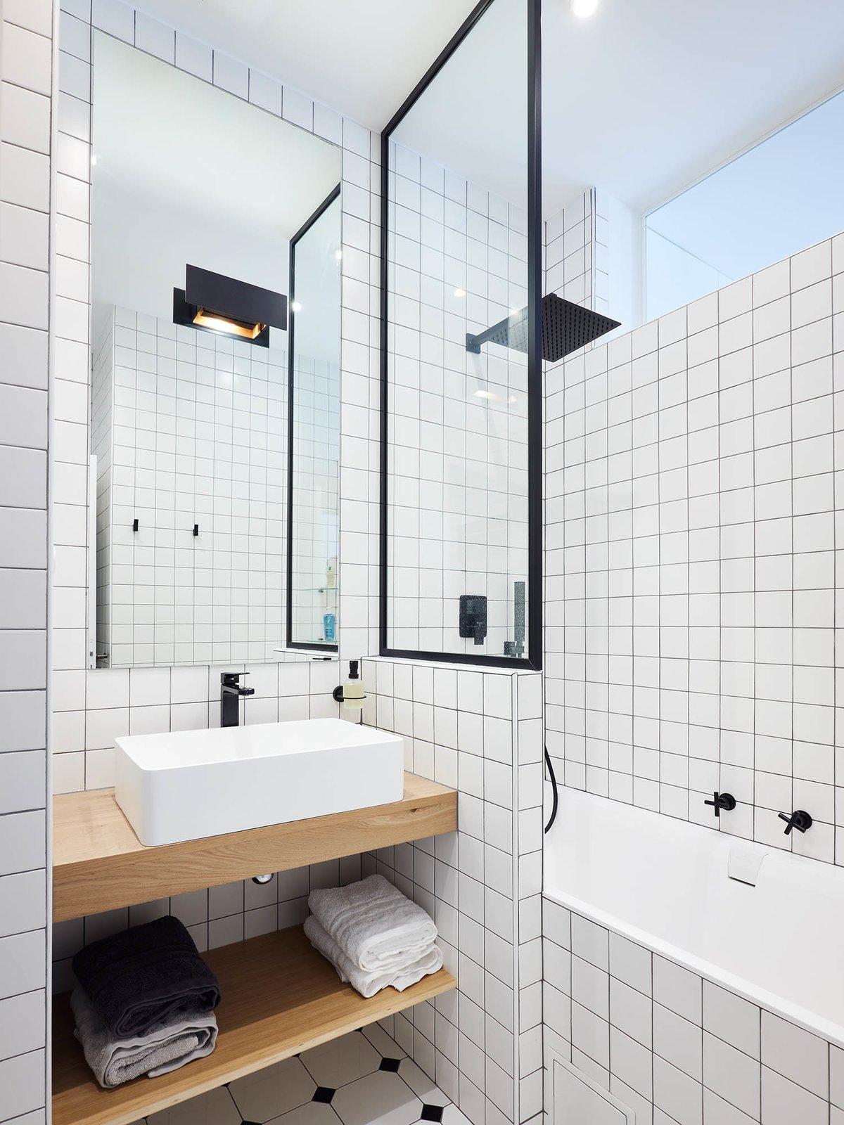Bath, Wood, Ceiling, Porcelain Tile, Porcelain Tile, Wall, Corner, Alcove, and Vessel To add balance and interest, the architect contrasted the texture of oak shelving with the sleek finish of glossy white tile in the bathroom.   Bath Corner Vessel Alcove Photos from Budget Breakdown: A Muddled Parisian Pad Gets a Sleek Makeover for $117K