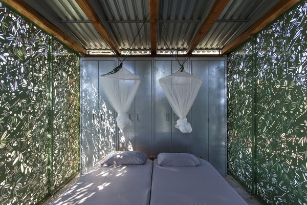 Mosquito nets suspend from the corrugated metal ceiling and provide protection from natural elements while resting or sleeping.