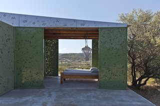 Sculptural olive trees frame the house, which is woven with its natural setting.