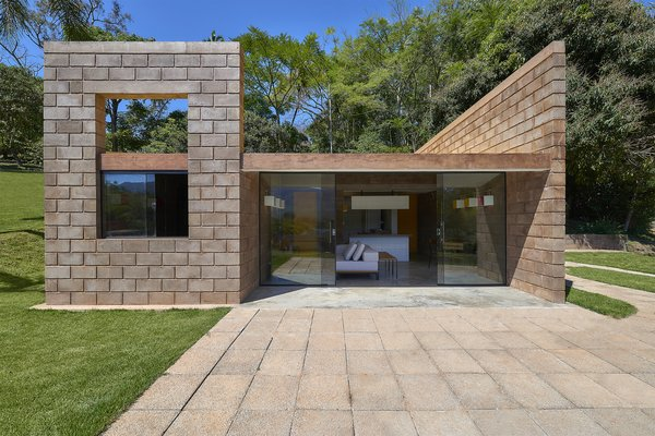 The home's exterior is composed of stacked blocks made from mining waste and concrete. A glass wall on the rear facade contrasts with the blocks and facilitates an indoor/outdoor connection.