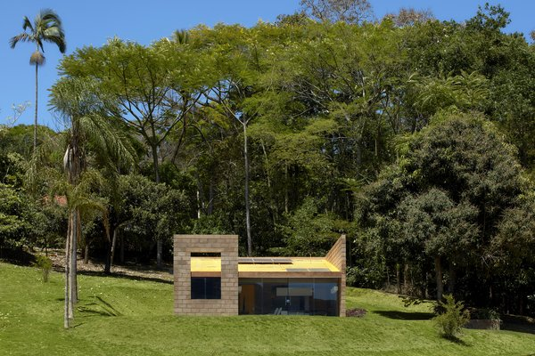 A yellow-painted sloping roof supports solar panels and helps to drain rainwater.