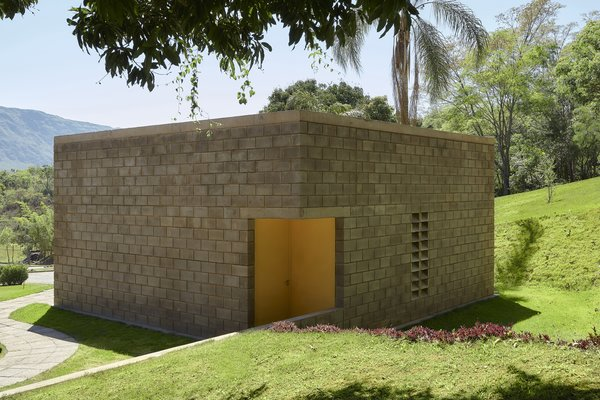 The house's cube-like form and its block siding create a strong geometric statement.