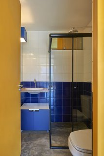 Cobalt blue wall tile brightens the bathroom and contributes to the home's palette, which juxtaposes earth tones with primary colors.