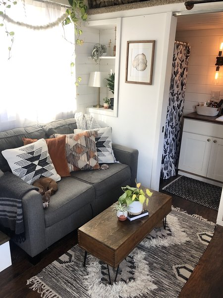 """""""Our living room is a mixture of new, thrifted, and handmade pieces,"""" Shaffer says. """"We made the coffee table; the top lifts up on hinges so we can use it to eat or put our laptops on it."""""""