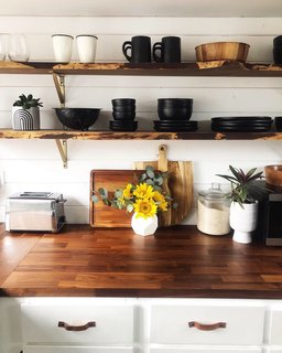Wood counters from Ikea and live-edge salvaged wood shelves from Salvage Works in Portland add warmth and texture in the light-filled kitchen.