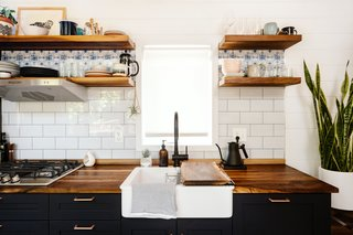 Walnut counters and open shelving complement dark blue-painted cabinetry and copper drawer pulls in the kitchen, where aluminum panels from Muraluxe give the impression of a tile backsplash.
