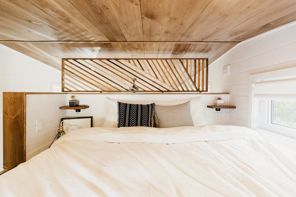 A wood screen lends privacy in the loft-style bedroom while still allowing for air to flow in and out of the space.