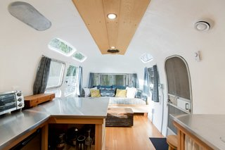 The interior of the Airstream was reimagined using reclaimed materials. The flooring is made of old-growth Douglas fir, and the ceiling features yellow cedar sawmill offcuts. Ryan crafted the built-in sofa using more cedar sawmill offcuts, while Catherine sewed the drapery and the upholstery, using fabric she collected from various thrift shops and IKEA.