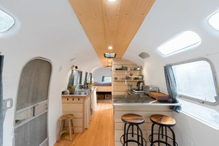 The couple outfitted the kitchen with stainless steel counters and cabinetry and shelving made from Douglas fir sawmill offcuts.