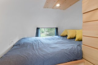 Homemade drapes and a built-in king-size bed make for a cozy sleeping area.