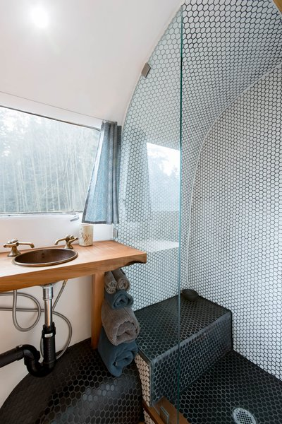 In the bathroom, hexagonal mosaic tile covers the floor and the shower walls. The vanity is made from a maple slab, and the sink and the fixtures are copper.