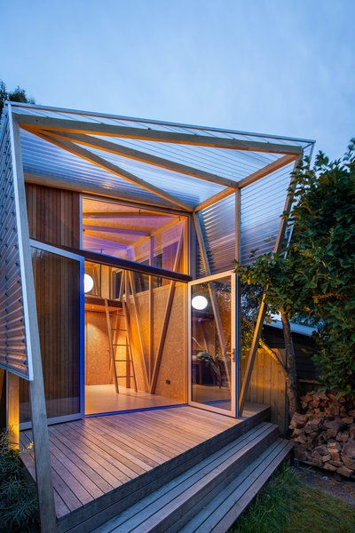 A pergola made of opaque, corrugated polycarbonate extends from the front facade and guards against bright sunlight, wind, and rain.