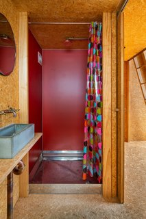 To create interest and a note of brilliance, Parsonson sided the shower walls with red Invibe panel board.