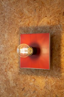 The architect designed a geometric wall sconce made from red Invibe panel board for the bathroom.