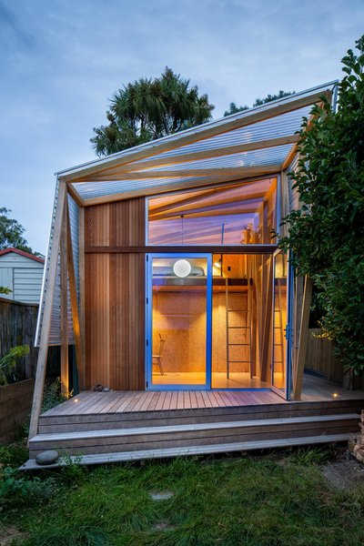 In the evening, interior lighting interacts with the polycarbonate pergola that extends from the front, creating a lantern-like glow.