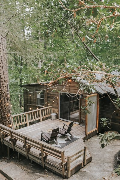 The Cobb Haus, a wood-sided, 700-square-foot cabin in Cobb, California, features a large wood deck surrounded by towering trees.