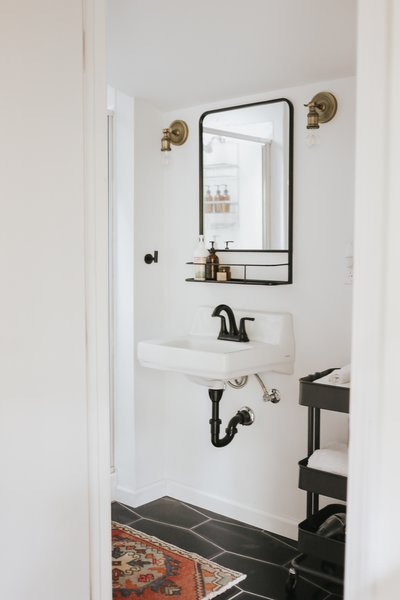 In recreating the bathroom, Mendes employed a wall-mounted sink, white-painted walls and black hexagonal floor tile.