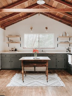Hope replaced the upper wood cabinets with open shelving and painted the lower cabinets a shade of gray-green. Beneath the linoleum were wood floors that the designer refinished.